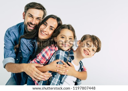 Power in big family. Dad and mommy hugging them beautiful kids and looking on the camera