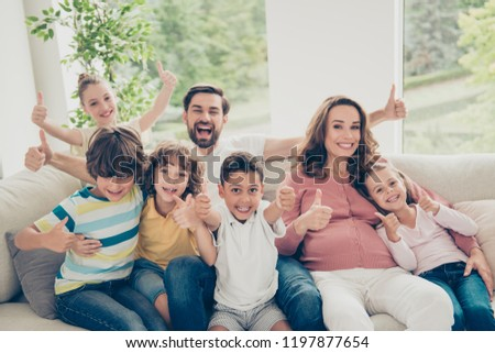 Free time concept. Close up photo nice, glad, positive, cheers large, full multiethnic family hispanic people demonstration or show thumb-up sit comfort, cozy sofa or couch in modern light interior #1197877654