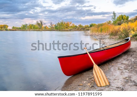 red tandem canoe with a wooden paddle on a lake shore, fall scenery #1197891595