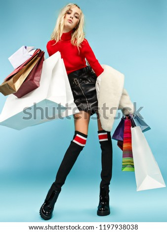 Full length portrait of a beautiful smiling funny blonde woman walking with colorful shopping bags isolated over blue studio background. The lifestyle, fashion, sale, shopaholic concept #1197938038