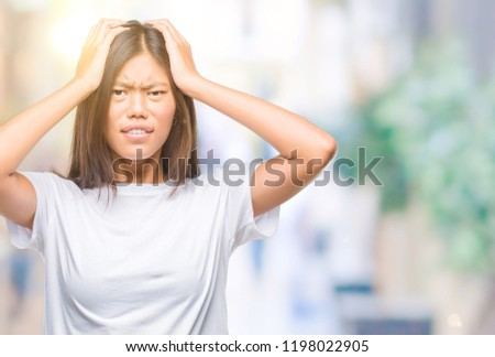 Young asian woman over isolated background suffering from headache desperate and stressed because pain and migraine. Hands on head. #1198022905