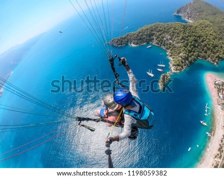 Paragliding in the sky. Paraglider tandem flying over the sea with blue water and mountains in bright sunny day. Aerial view of paraglider and Blue Lagoon in Oludeniz, Turkey. Extreme sport. Landscape #1198059382