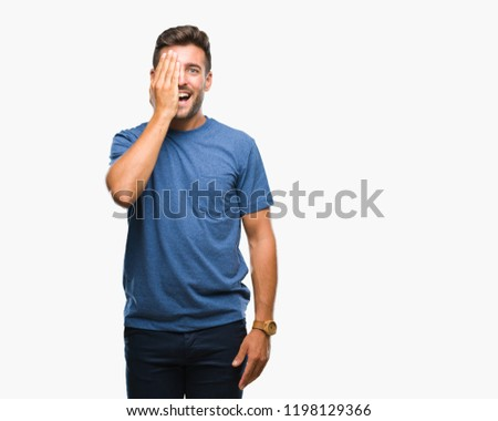 Young handsome man over isolated background covering one eye with hand with confident smile on face and surprise emotion. #1198129366