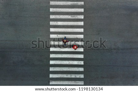 Aerial. Two pedestrians walk on a pedestrian crossing. #1198130134
