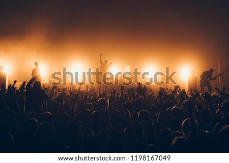 silhouettes of concert crowd in front of bright stage lights. A sold out crowd on rock concert. Crowd of fans at music festive. Party in nightclub. #1198167049