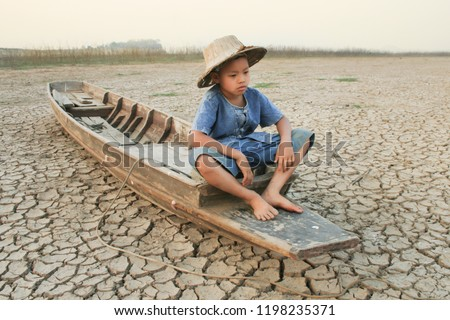 Children sitting on boat at dry river with sad and hopeless face metaphor climate change, water crisis and world environment #1198235371