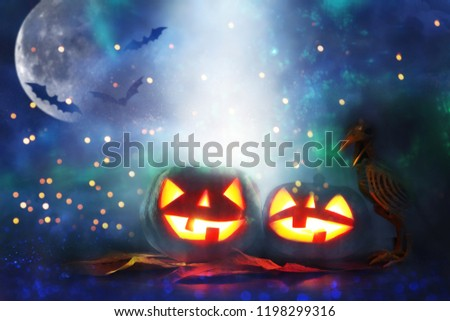 Halloween holiday concept. Pumpkins over wooden table at night scary, haunted and misty forest #1198299316