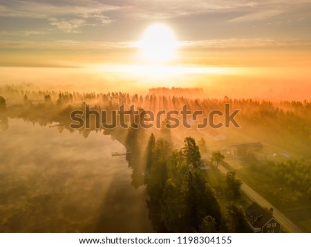 drone photo of foggy sunrise over forest, lake an village in North Sweden - golden sun light with beams and shadows. Västerbotten,  West Bothnia province, north of Sweden #1198304155