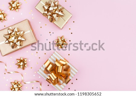 Fashion gifts or presents boxes with golden bows and star confetti on pink pastel table top view. Flat lay composition for birthday, christmas or wedding. #1198305652