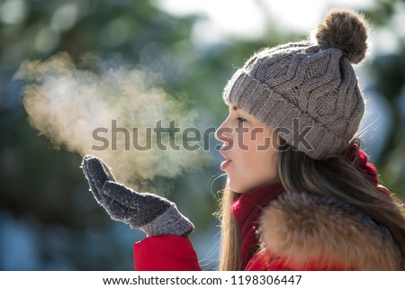Attractive young woman breathe out steam outdoor in winter Royalty-Free Stock Photo #1198306447