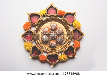 Diwali Rangoli using Diya, flowers and Motichoor Laddu or Boondi Laddoo arranged over white background, selective focus #1198316908