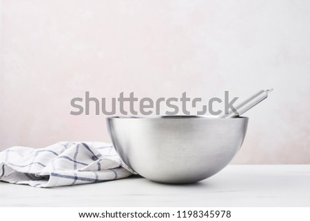 Baking concept. Bowl with a whisk and dishcloth on white marble table over pink background with copy space. #1198345978