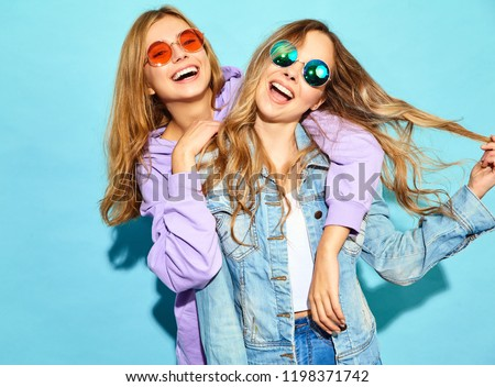 Two young beautiful blond smiling hipster girls in trendy summer clothes. Sexy carefree women posing near blue wall in sunglasses. Positive models having fun