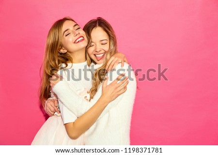 Two young beautiful smiling hipster girls in trendy summer white clothes. Sexy carefree women posing near blue wall. Positive models hugging #1198371781