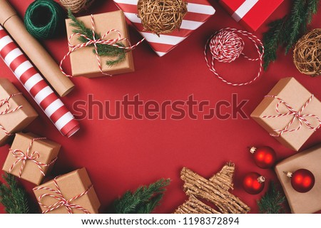 Christmas background with gift boxes, clews of rope, paper's rools and decorations on red. Preparation for holidays. Top view with copy space. #1198372894