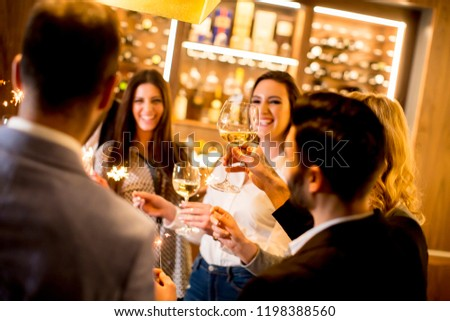 Group of young people toasting with white wine at home #1198388560