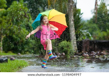 Kid playing out in the rain. Children with umbrella and rain boots play outdoors in heavy rain. Little girl jumping in muddy puddle. Kids fun by rainy autumn weather. Child running in tropical storm. #1198404997