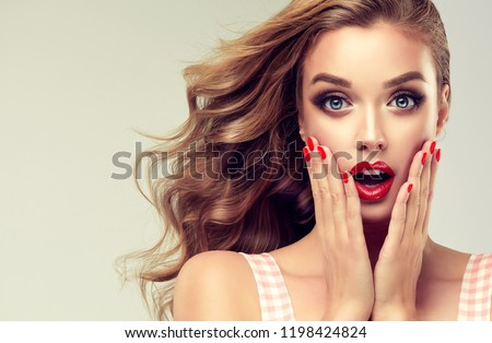 Woman with red lips and nails surprise holds cheeks by hand .Beautiful girl  with curly hair surprised and shocked looks on you . Presenting your product. Expressive facial expressions  #1198424824