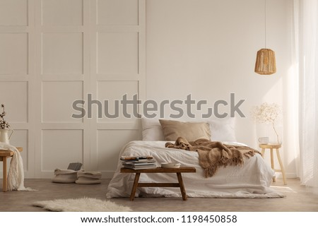 Natural blanket on white bed in simple bedroom interior with fur next to wooden stool. Real photo #1198450858