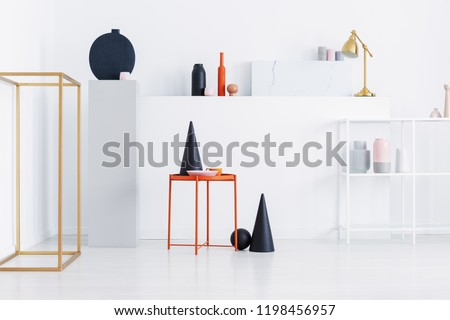 Real photo of black cone, pink plate, orange coffee cup on metal table on display of shop with modern art #1198456957