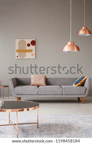 Real photo of a minimalistic living room interior with a sofa, copper table and chandelier #1198458184