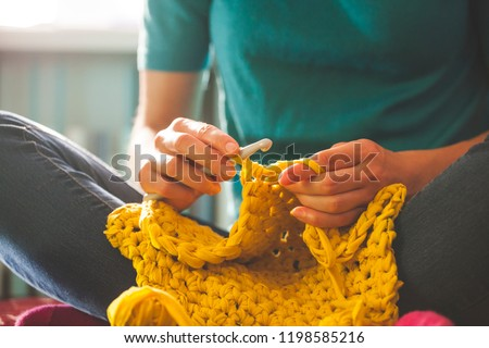 Woman knits crochet. The girl sits on the couch and knits from knitting yarn. Crochet thick threads. Home comfort. #1198585216