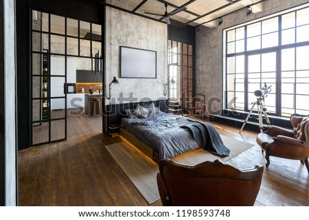 luxury studio apartment with a free layout in a loft style in dark colors. Stylish modern kitchen area with an island, cozy bedroom area with fireplace and personal gym #1198593748