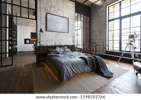 luxury studio apartment with a free layout in a loft style in dark colors. Stylish modern kitchen area with an island, cozy bedroom area with fireplace and personal gym #1198593766