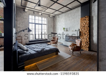 luxury studio apartment with a free layout in a loft style in dark colors. Stylish modern kitchen area with an island, cozy bedroom area with fireplace and personal gym #1198593835