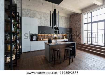 luxury studio apartment with a free layout in a loft style in dark colors. Stylish modern kitchen area with an island, cozy bedroom area with fireplace and personal gym #1198593853