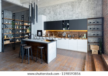 luxury studio apartment with a free layout in a loft style in dark colors. Stylish modern kitchen area with an island, cozy bedroom area with fireplace and personal gym #1198593856