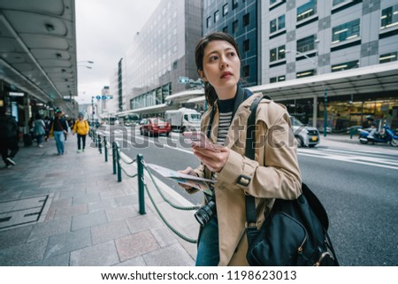 elegant female traveler standing on the street and using smartphone to check the route of her plan. backpacker using online map app. busy Japanese city lifestyle. #1198623013