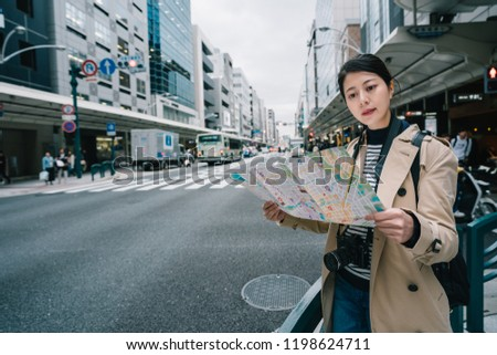 elegant female backpacker looking at the map and thinking where else is worth to visit. traveler standing in the city street in Japan. sightseeing in Kyoto. #1198624711