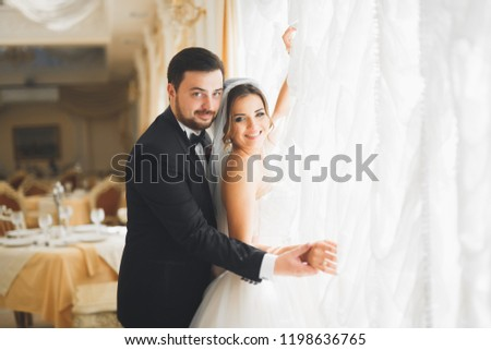Gorgeous groom gently hugging stylish bride. Sensual moment of luxury wedding couple #1198636765