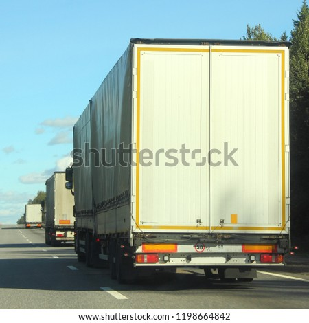 Heavy duty transportation in logistics - three white semi-trailer trucks rides on asphalt highway in summer against green trees, road signs and blue sky, rear-side view #1198664842