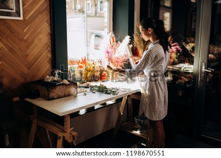 Florist dressed in a striped dress stands near the table with colorful dried flowers and holds transparent packaging envelope in the flower shop #1198670551
