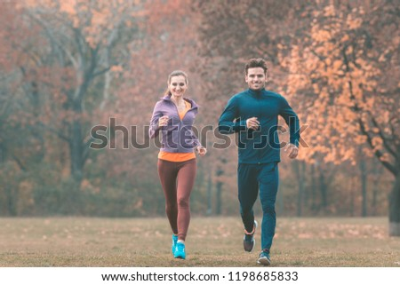 Couple in wonderful fall landscape running for better fitness towards the camera #1198685833