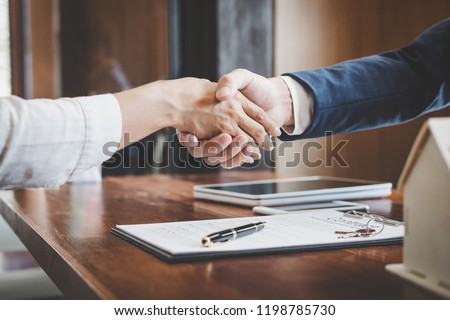 Real estate agent and customers shaking hands together celebrating finished contract after about home insurance and investment loan, handshake and successful deal. #1198785730