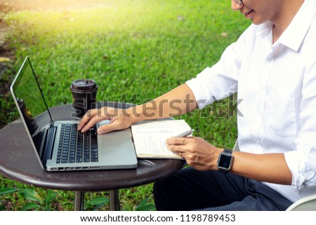 young buseness man work on the table with his laptop and coffee in garden outdoor loaction #1198789453