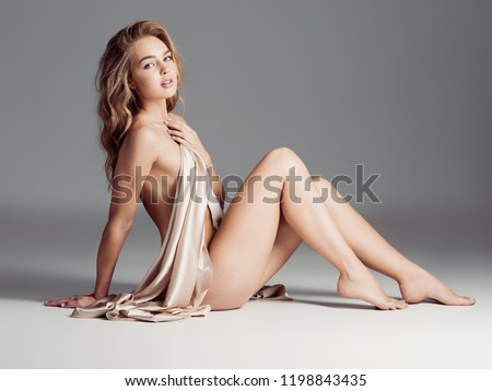 Sexy fit naked woman with healthy clean skin sitting at studio. Beautiful perfect female body of pretty young caucasian girl. #1198843435
