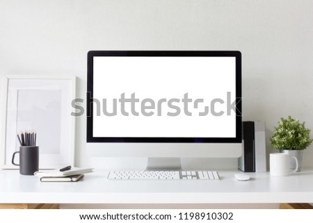 Front view office table desk. Workspace with blank computer screen, keyboard, mouse, booklets, pen, pencil, white picture frame , plant mockup, cups, books and white background