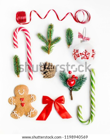 Flat lay Christmas composition with fir tree branches, gingerbread Christmas Cookie  and holiday ornament on white background. Top view.  Royalty-Free Stock Photo #1198940569