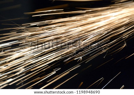 Abstract background. Glowing streaks of light. Rays of light in the dark. Fireworks / Explosion / Sparks. Exposure. Carpentry workshop. Hardware.  #1198948690