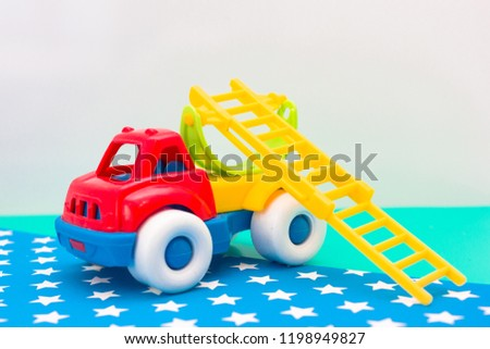 Toy fire truck on a blue and green background with asterisks