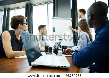 Discussing company progress. Confident young man standing near whiteboard and pointing graph while his colleagues sitting at the desk #1198952788