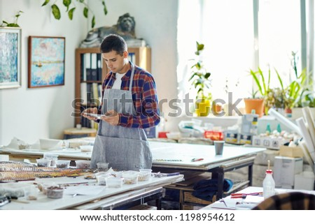 Young man in apron using tablet while standing near table with mosaic in modern workshop #1198954612