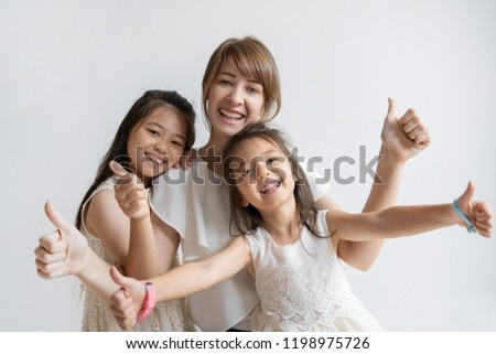 Positive Caucasian mother and daughters showing thumbs up and smiling. Cheerful family of three looking in approval. Happy event concept.  #1198975726