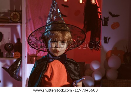 Little cute Halloween wizard. Magic hat. Children play with pumpkins and treat. Secrets of Magic. Holiday concept. Happy halloween #1199045683