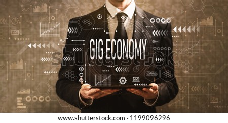 Gig economy with businessman holding a tablet computer on a dark vintage background #1199096296