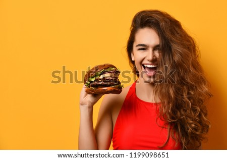 Woman hold big barbecue burger sandwich with hungry mouth happy screaming laughing on yellow background. Fast food concept.  #1199098651